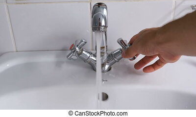 Man Washing Hands in the Sink under Running Water from the...