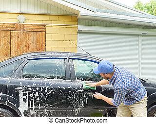 Man washing his black car near house.