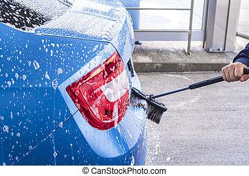 Man washing his car in a self-service car wash station.A man washes a car on his own. Car wash self-service. Cheap car wash.