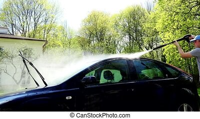 Man washing his car with using a high pressure water jet.