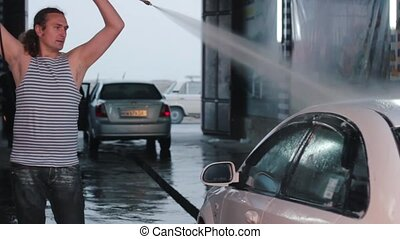 Man washing his car with water spray from high pressure washer. Car wash self-service. Caucasian man.