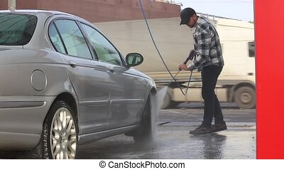 Man washing his car with water spray from high pressure washer. Car wash self-service.