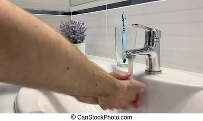 Man washing his hands under the faucet in the bathroom