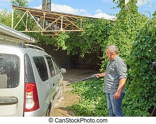 Man washing his silver car near house.