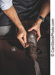 man washing leather brogues with a sponge - hands of an...