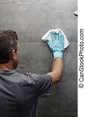 Man Washing Shower Wall with a Rag While Wearing a Green Protective Glove