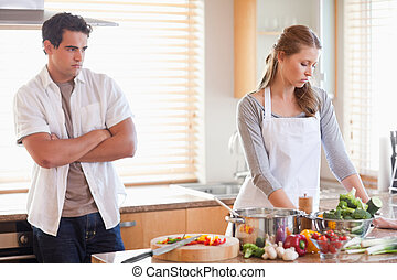 Man watches his girlfriend cooking