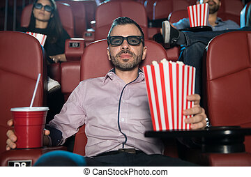 Man watching a 3d movie with some popcorn
