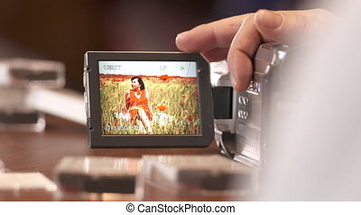 Man watching family home video on LCD screen of digital Mini...
