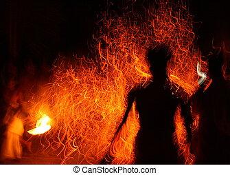 Man watching fire rituals at night.