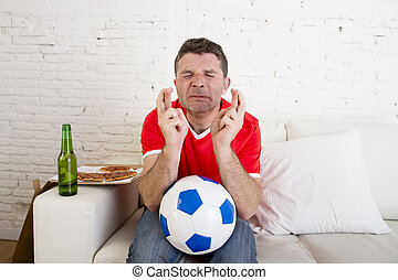 man watching football on tv nervous and excited suffering stress crossing fingers for goal