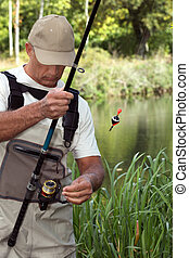 man watching his fishing rod in front of a river