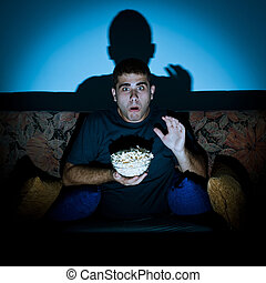 Man watching horror movie - Man watching and scared by...