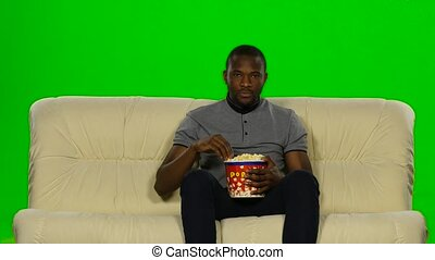 Man watching movie on couch and eating popcorn. Green screen