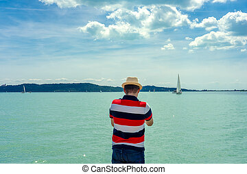 man watching sailboats from the coast at Balaton Lake Hungary