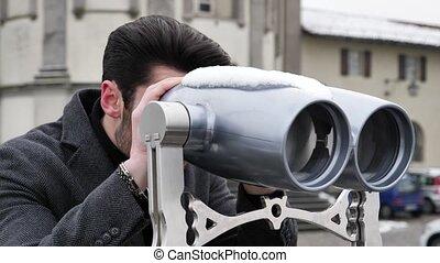 Man watching sights through binoculars - Back view of...