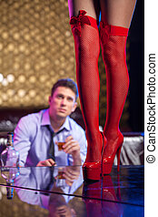 Man watching striptease dancer in red hose. Close up of...
