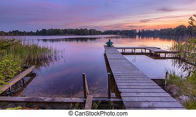 Man watching sunset - Man sitting on Wooden swimming pier on...