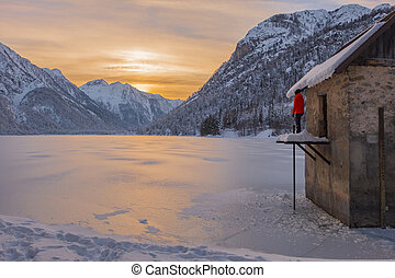 Man watching sunset over mountains and lake Predil in winter...