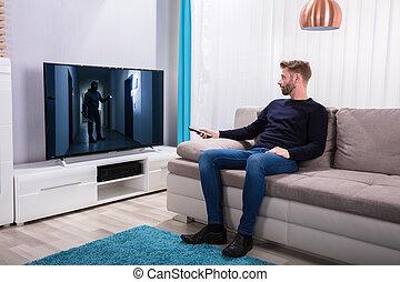 Man Watching Suspense Movie On Television