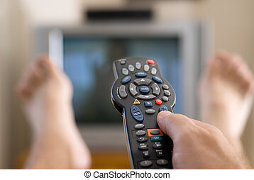 A man watches television and changes channels while relaxing on a Sunday afternoon.