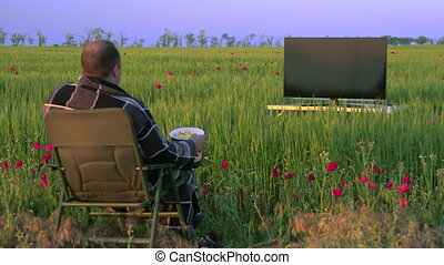 Man watching television in the green field