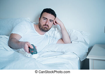 Man watching television lying in bed
