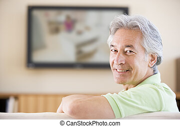 Man watching television smiling