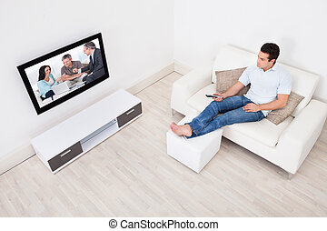 Young Man At Home Watching Movie On Television