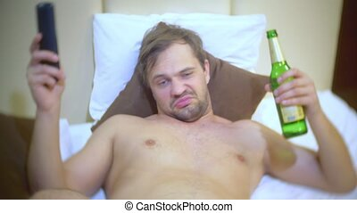 Man watching tv and drinking beer At home on a bed. 4k.