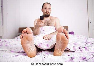 Man watching TV from the bed with remote-control