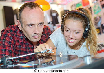 Man watching young lady putting vinyl record playing