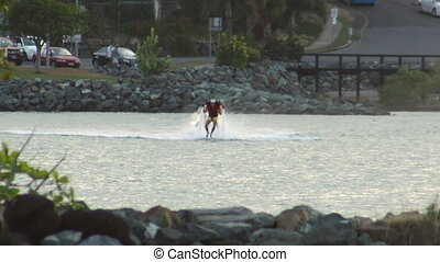 Man water jet packing - A wide shot of a man on a water jet...