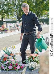 man watering flowers in cemetery