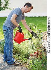 man pouring water at garden with watering can