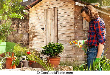 Man watering plants with hosepipe in the backyard
