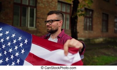 Man waving a US flag while walking along the street - the concept of Independence Day USA