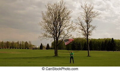 Man waving American flag on a glade