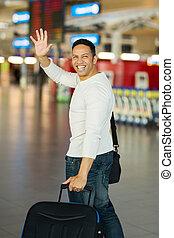 man waving goodbye at airport