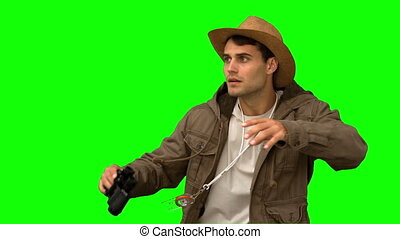 Man wearing a coat using binoculars on green screen in slow...