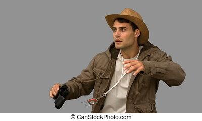 Man wearing a coat using binoculars on grey screen in slow...
