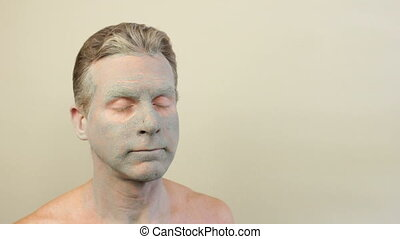 Man Wearing a Green Clay Mask - Adult caucasian male wearing...