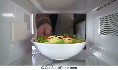 Man wearing a robe heating up cooked pasta dish in the microwave oven