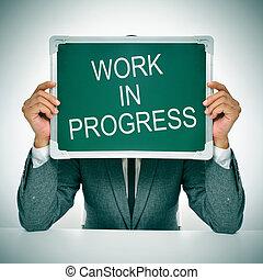 work in progress - man wearing a suit sitting in a table...