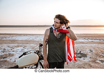 Man wearing american flag cape and golden helmet posing