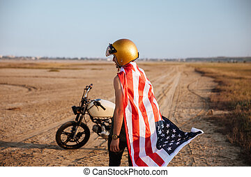 Man wearing american flag cape and golden helmet