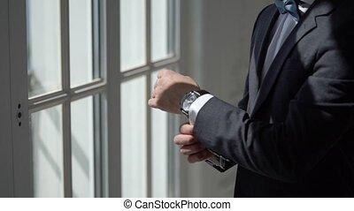 Man wearing and buttoning jacket near window