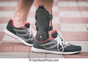 Man wearing ankle brace - Man in athletic sneakers wearing...
