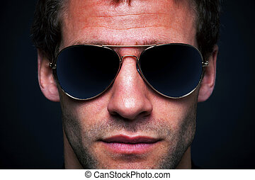 Close up portrait of a man wearing gold rimmed aviator sunglasses, clipping path for the lenses to add your own reflection.
