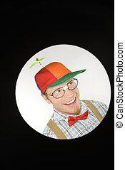 Close up circle vignett of Caucasian young man dressed like nerd wearing propeller hat looking mischievous.